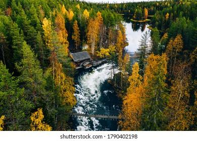Vue aérienne de la rivière rapide avec pont suspendu et cabane en bois dans la belle forêt d'automne orange et rouge. Parc national d'Oulanka, Finlande.