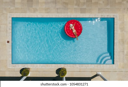 Aerial view of female in bikini lying on a floating mattress in swimming pool with her face covered with hat. Top view of woman sunbathing on inflatable mattress in pool.