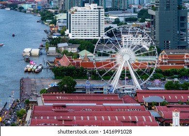 Aerial view of the ferris wheel, Asiatique The Riverfront, near Chao Phraya River with skyscraper buildings in Bangkok Downtown at sunset, urban city, Thailand.