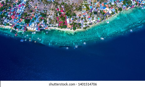 Aerial view of Filipino boats floating on top of clear blue waters, Moalboal is a deep clean blue ocean and has many local Filipino boats in the sea. Moalboal, Cebu, Philippines.