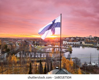 Aerial view of Finnish flag on the tower of Town Hall against the red sunrise sky in Joensuu, Finland.