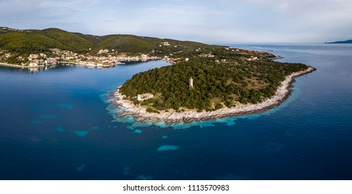 Aerial view of the Fiscardo fishing village and Venetian lighthouse on Kefalonia island