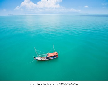 Aerial view of fishing boat on emerald sea