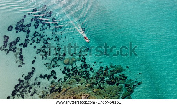 Aerial view of a fishing boat sailing in the Mediterranean Sea close to the seashore