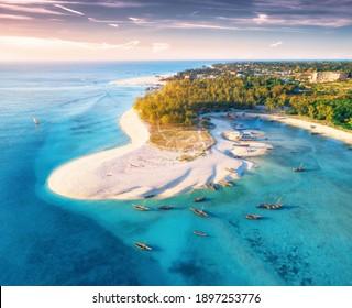Luftsicht auf die Fischerboote an der tropischen Küste mit Sandstrand bei Sonnenuntergang. Sommerreisen in Sansibar, Afrika. Draufsicht auf Boote, Yachten, grüne Palmen, klares blaues Wasser, bunter Himmel