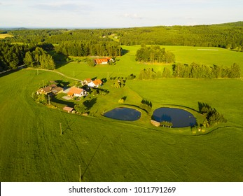 Aerial view of fishing ponds and farmhouses. System of ponds on the brook. Traditional fish farming agriculture. South Bohemia countryside from above. Czech republic, European union.