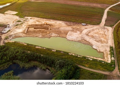 Aerial view of fishpond construction site from drone pov with excavator machinery and large pool of water