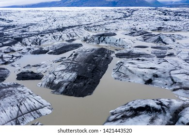 Aerial view of floating icebergs from glacier melt into the lake water as a result of global warming, seen from a drone above. Svinafellsjokull lake, Vatnajokull National Park, Iceland
