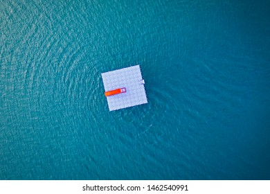 Aerial view of floating platform with a red slide on calm sea water.