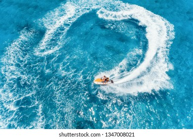 Aerial view of floating water scooter in blue water at sunny day in summer. Holiday in Indian ocean, Zanzibar, Africa. Top view of jet ski in motion. Tropical seascape with moving motorboat. Extreme