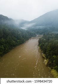Aerial view of flooded Karamea river West Coast New Zealand in tempered rainforest on a moody foggy winter day and brown water due to high water level