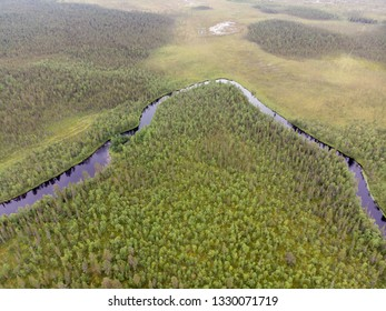Aerial view of flowing river in beautiful autumn forest landscape in Pallas-Yllastunturi National Park, Kittila Finland