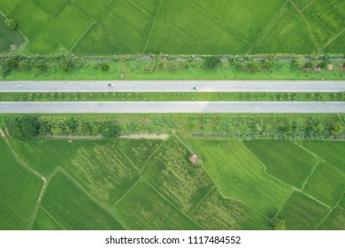 Aerial view from flying drone. Top view asphalt road in the middle of green young rice fields in Thailand