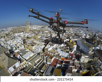 An aerial view of a flying multi-copter with raised landing gears and a camera with slightly blured center of old Seville in the background