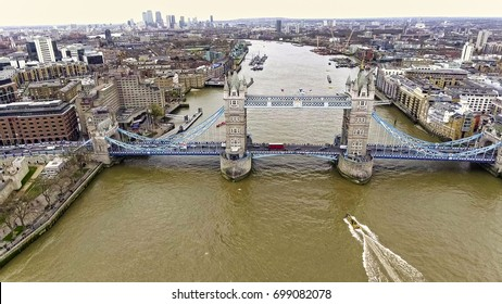 Aerial View of Flying Over Tower Bridge and River Thames in London, UK feat. Skyscrapers and Business Office Buildings in the Background with Boats and Car Transportation Vehicles