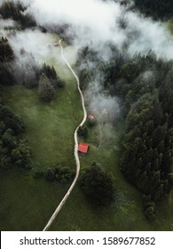 Aerial view of foggy forest,mountain road  to small cabin in the wilderness after storm during summer.Vintage,travel concept. Germany,Europe.
