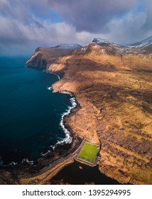 Aerial view of a football field from above with scenic mountain range covered in snow near the village Eidi (Faroe Islands, Denmark, Europe)