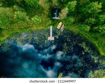 Aerial view of forest and blue lake with clouds reflection in Finland. Sauna house by the lake shore. Wooden pier with fishing boats.