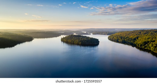 Aerial view of forest and an island on a lake and during sunrise