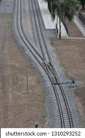 Aerial view of forking railway tracks with posts and tidy platform under green trees.
