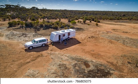 Aerial view of four wheel drive vehicle and caravan camped in the outback of Australia.