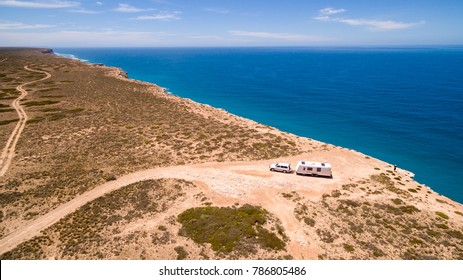 Aerial view of Four wheel drive vehicle and caravan parked next to cliffs at the Great Australian Bight.
