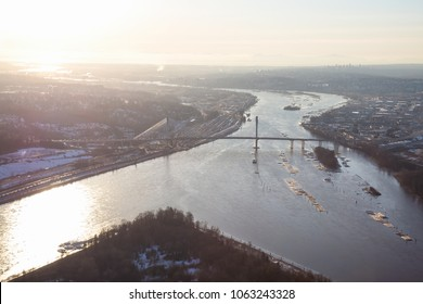 Aerial view of Fraser River and Port Mann Bridge during a vibrant winter sunset. Taken in Greater Vancouver, British Columbia, Canada.