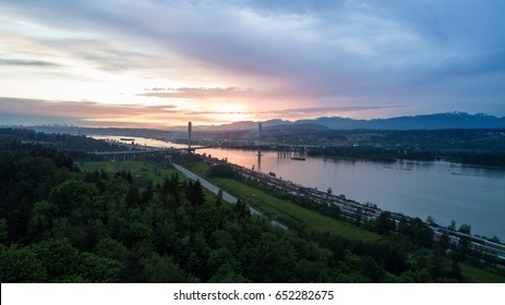 Aerial view of Fraser River and Port Mann Bridge from Surrey, Greater Vancouver, BC, Canada, during a cloudy sunset.