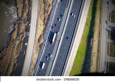 An aerial view of a freeway beside some water.