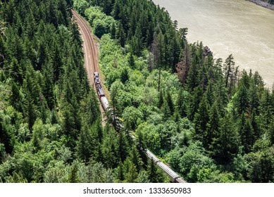 Aerial View of a Freight Train on a Railway Line Running Through a Forest alongside a River on a Sunny Summer Day. Fraser River Valley, BC, Canada.