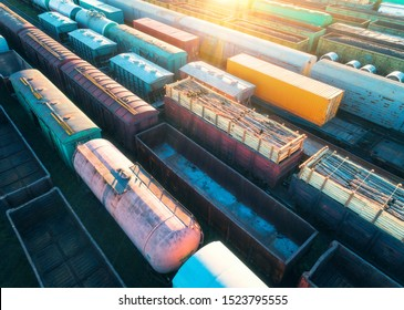 Aerial view of freight trains. Colorful cargo wagons on railway station. Wagons with goods on railroad. Heavy industry. Industrial landscape with train, railway platfform at sunset. Top view. Depot