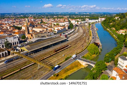 Aerial view of French city of Agen overlooking railway tracks on bank of Garonne canal on summer day