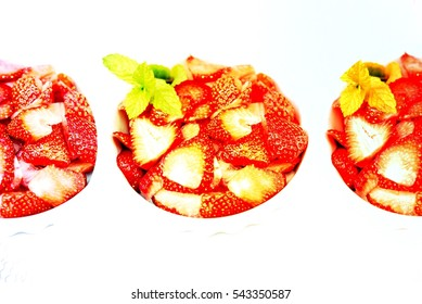 Aerial view fresh aromatic red strawberries cutted in thin slices Healthy fruits in white bowl with green mint leaves on white background for creative food concept Image with  filter effect