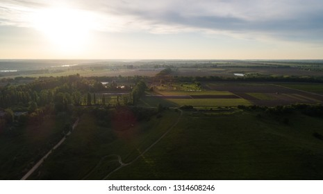 Aerial view of the fresh bright green lush countryside with green fields with patterns from the tractor at sunset.