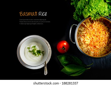 Aerial view of fresh Indian Basmati coloured rice with fresh salad, natural yoghurt and tomatoes against a dark background. Extended copy space.