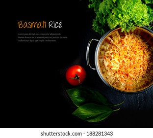 Aerial view of fresh Indian Basmati coloured rice with fresh salad and tomatoes against a dark background. Extended copy space.