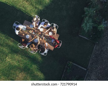 Aerial view of friends toasting drinks at outdoor party in restaurant. Group of people sitting around a table in garden and having drinks..