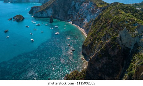 Aerial view of Frontone beach in Ponza, in Italy. This is a small bay of an island overlooking the Mediterranean Sea. The beach is full of people.
