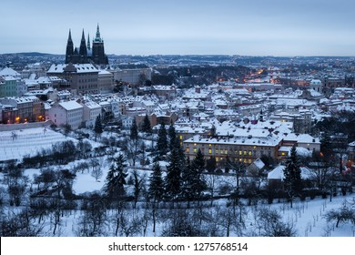 Aerial view of frozen winter city of Prague. Prague Castle with snow covered roofs in the early morning.