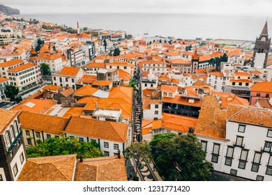 Aerial view of the Funchal old town - the capital of Madeira island during cloudy weather. Small houses with orange rooftops by the Atlantic ocean.