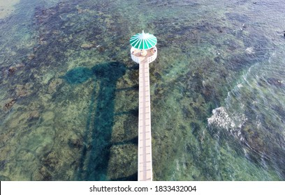 Aerial view of a gazebo standing over the seawater and connected by a bridge to the shore on a sunny summer day, in Xiaochijiao, Xiyu Township, Penghu, Taiwan