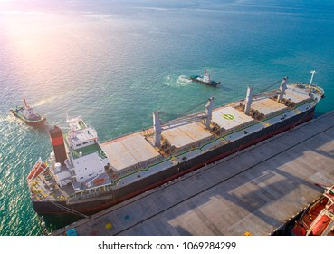 aerial view of general bulk cargo ship vessel on departure unberthing from the sea port terminal, safety circumstance sailingh by tug boats assist pull towage under navigation command pilot