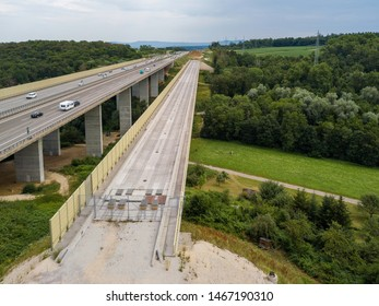 Aerial view of a German Autobahn with construction works for a new railway bridge next to it. Drone photo taken at Denkendorf near Stuttgart - on a weekend, hence not much truck traffic.