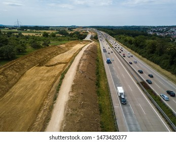 Aerial view of a German Autobahn with construction works for a new railway track next to it. Drone photo taken at Denkendorf near Stuttgart - on a weekend, hence not much truck traffic.