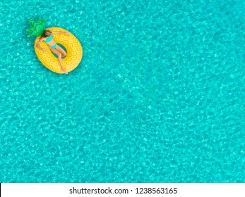 Aerial view of girl floating on inflatable pineapple mattress.