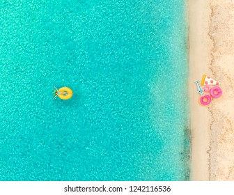 Aerial view of girl floating on inflatable pineapple mattress by sandy beach and inflatable rings.
