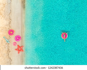 Aerial view of girl floating on inflatable donut mattress by sandy beach and inflatable rings.