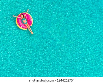 Aerial view of girl floating on inflatable donut mattress.