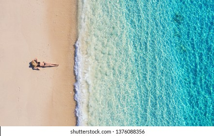 Aerial view of a girl on the beach on Bali, Indonesia. Vacation and adventure. Beach and turquoise water. Top view from drone at beach, azure sea and relax girl. Travel and relax - image