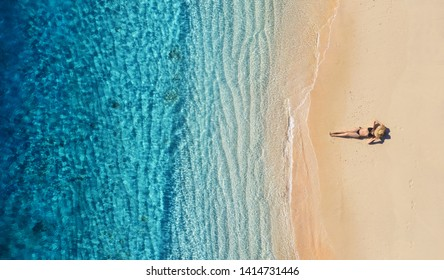 Aerial view of a girl on the beach. Vacation and adventure. Beach and turquoise water. Top view from drone at beach, azure sea and relax girl. Travel and relax - image